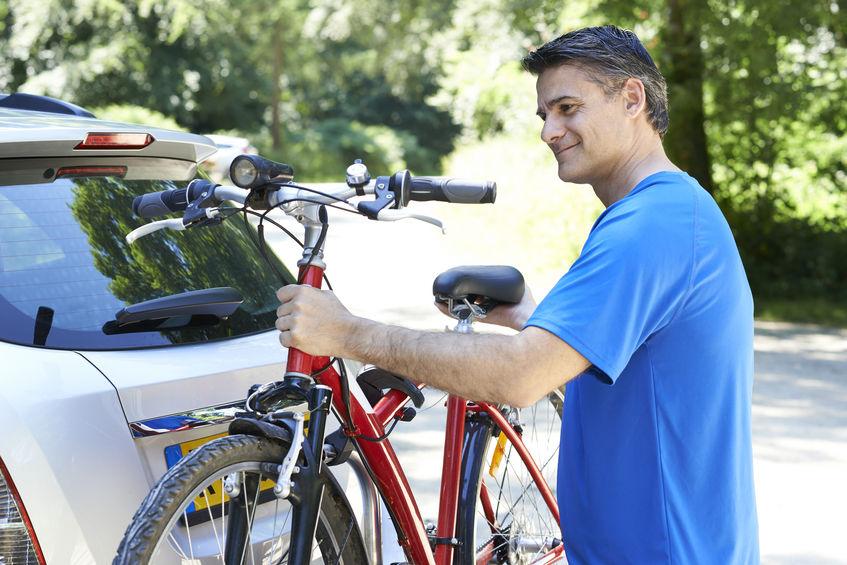 uomo più anziano che trasporta la sua mountain bike in auto