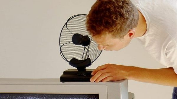 Uomo che sistema l'antenna TV da interno