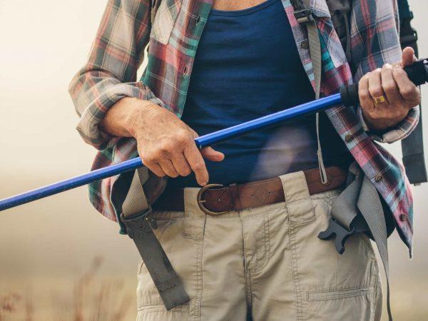 Persona che regge un bastoncino da trekking