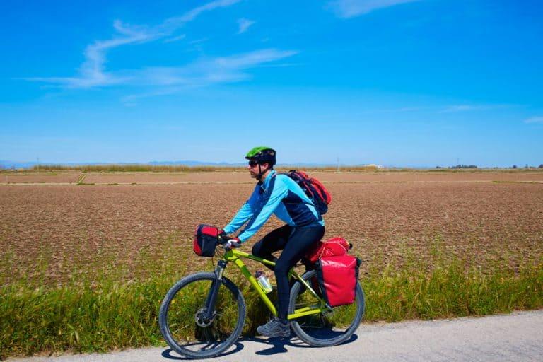 Uomo in bicicletta con varie borse