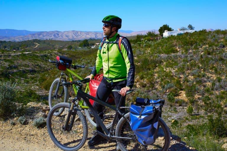 Uomo che sorregge una bici con delle borse