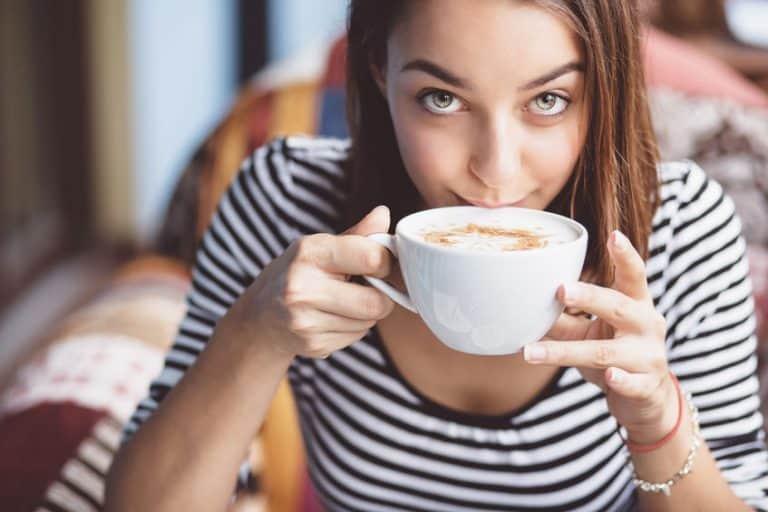 Donna che beve il cappuccino