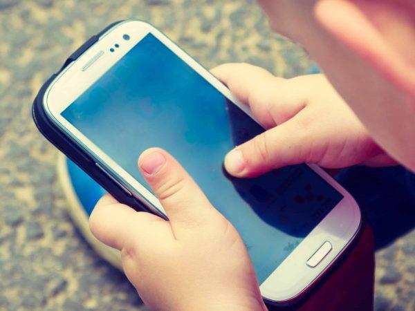 Bambino con cellulare in mano