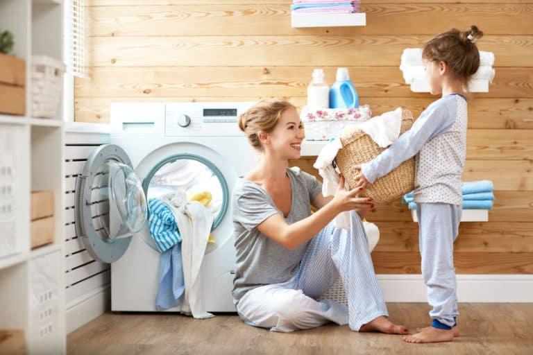 Donna e bambini vicino a una lavatrice