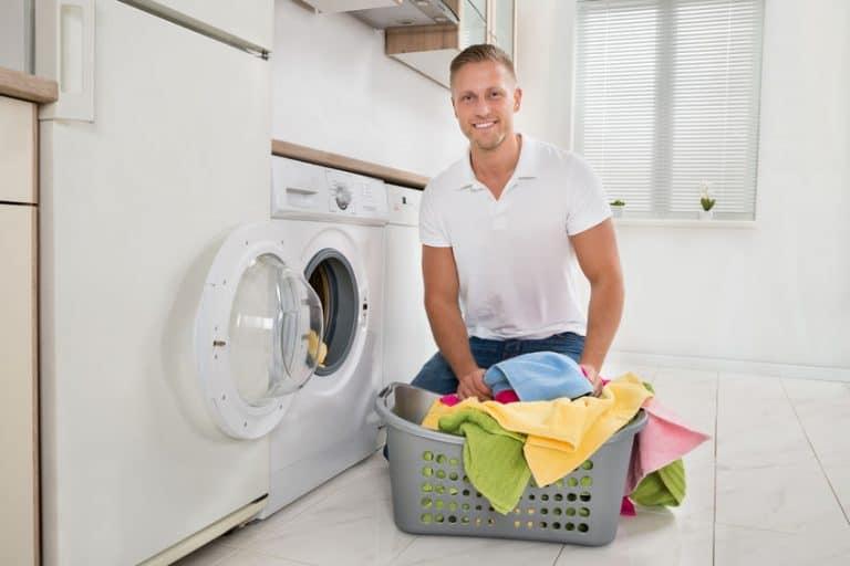 Un uomo davanti alla lavatrice