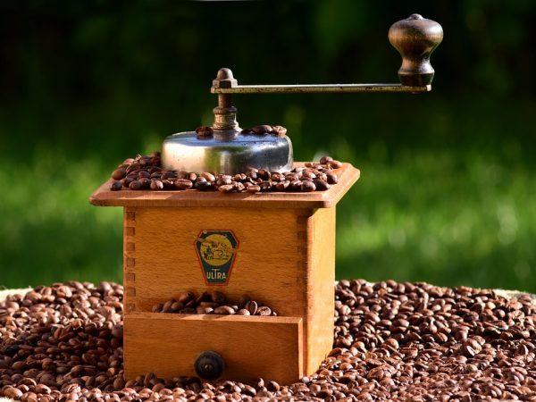 Un vecchio macinacaffè con chicchi di caffè