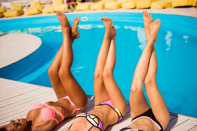 Tre donne in piscina con le gambe alzate