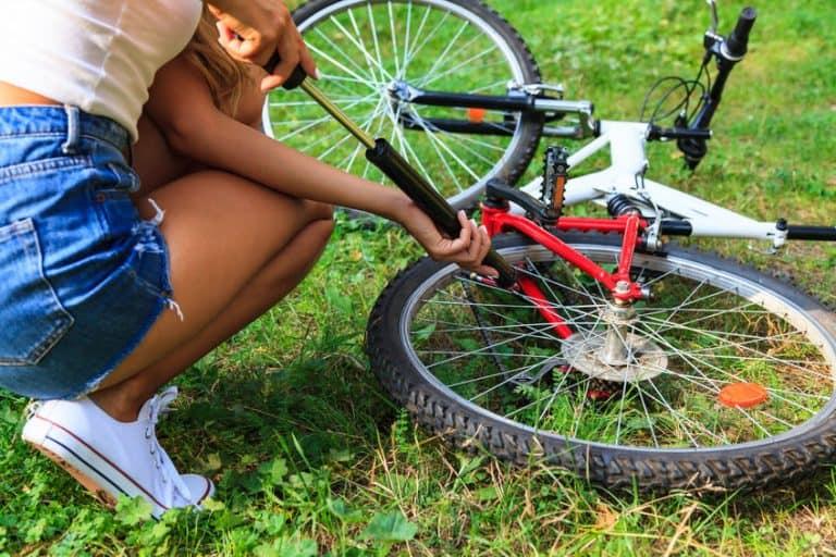 Ragazza che gonfia la ruota della bicicletta