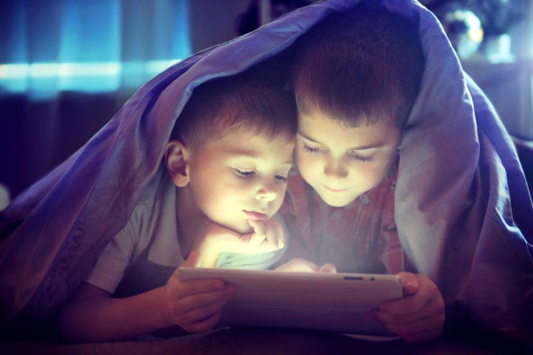 Bambini che guardano un tablet sotto le coperte