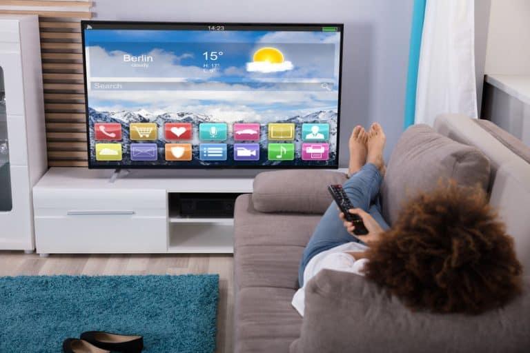 Donna sul divano che guarda la televisione