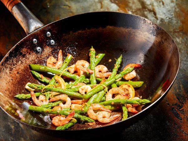 Un wok con gamberetti e asparagi