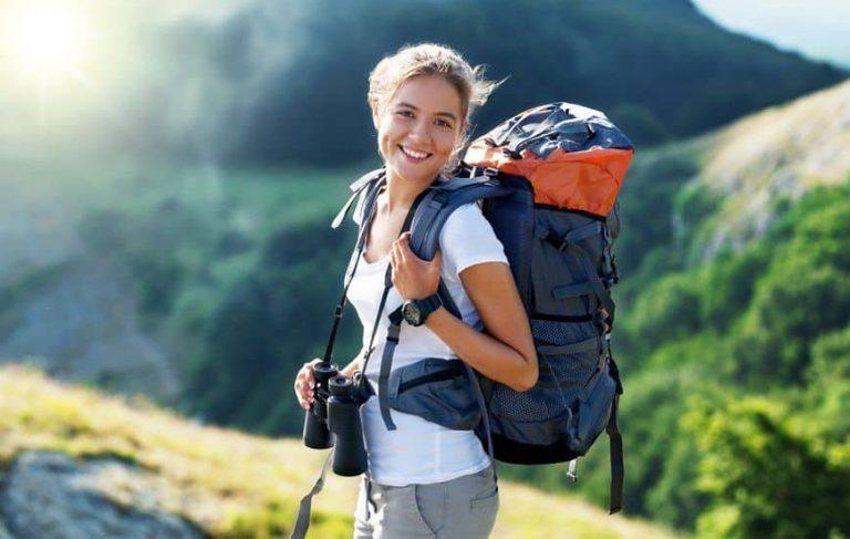 Donna che sorride con lo zaino sulle spalle