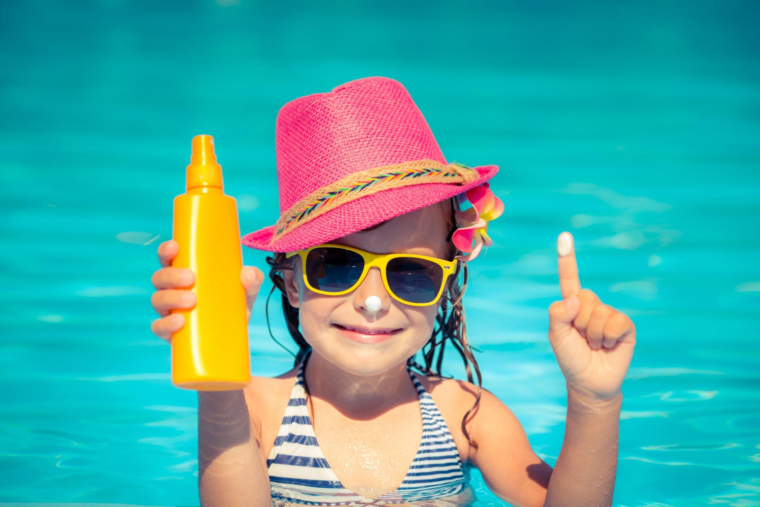Una bambina con la crema solare