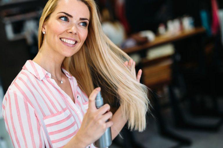 Donna bionda che si spruzza un termoprotettore sui capelli