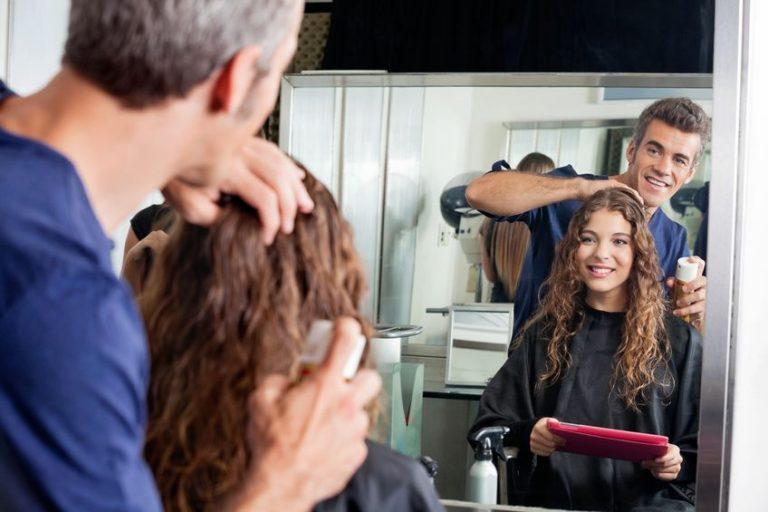 Parrucchiere che applica un termoprotettore sui capelli di una ragazza