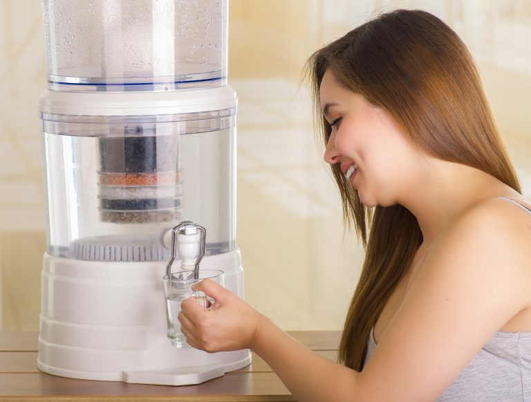 Donna che prende l'acqua da un depuratore dispenser