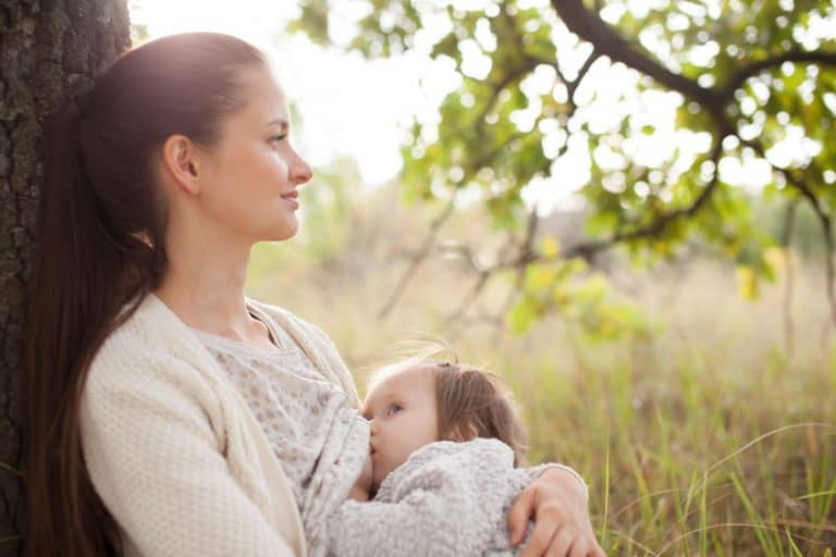 Donna che allatta appoggiata ad un albero