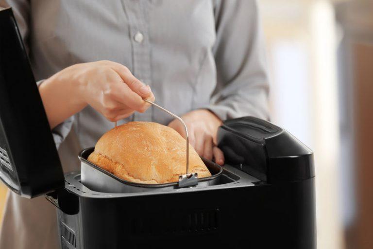 Donna che tira fuori il cestello della macchina del pane