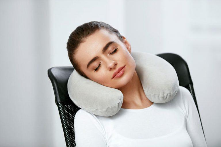 Donna che usa il cuscino per la cervicale
