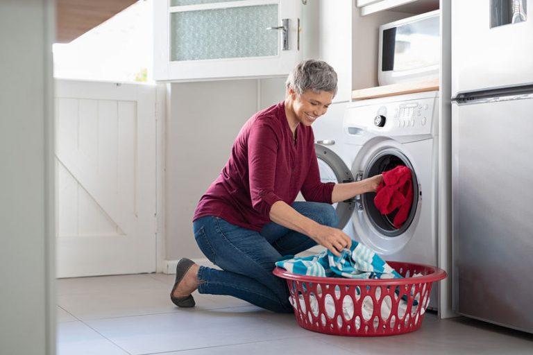 Donna che mette i panni dentro un'asciugatrice