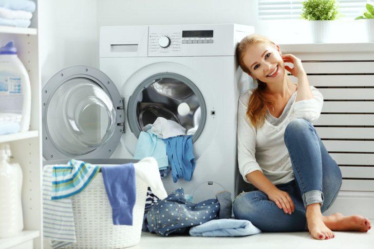 Donna seduta accanto alla lavatrice