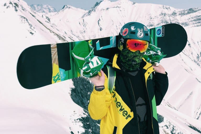 Uomo con tavola da snowboard sulle spalle