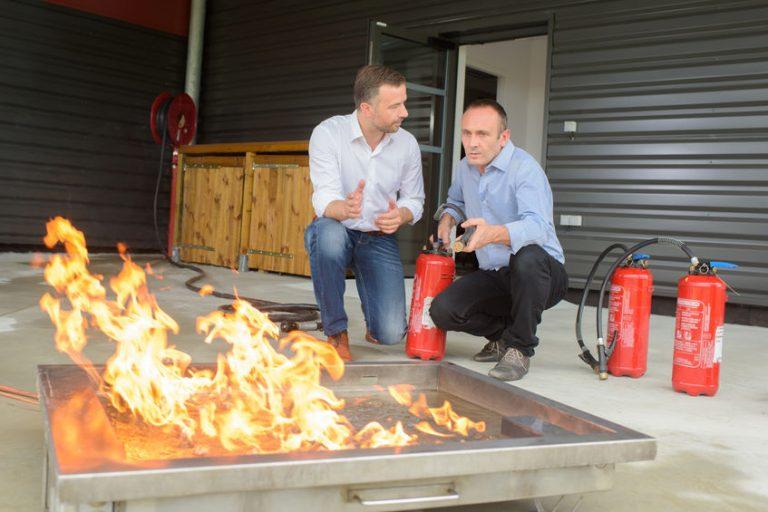 Uomini con estontore davanti a un fuoco