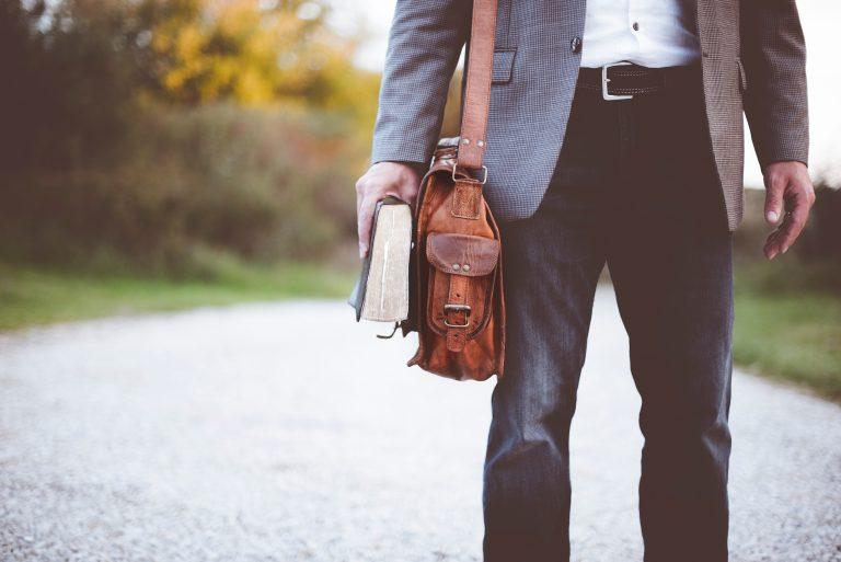 Uomo con borsa e un libro in mano