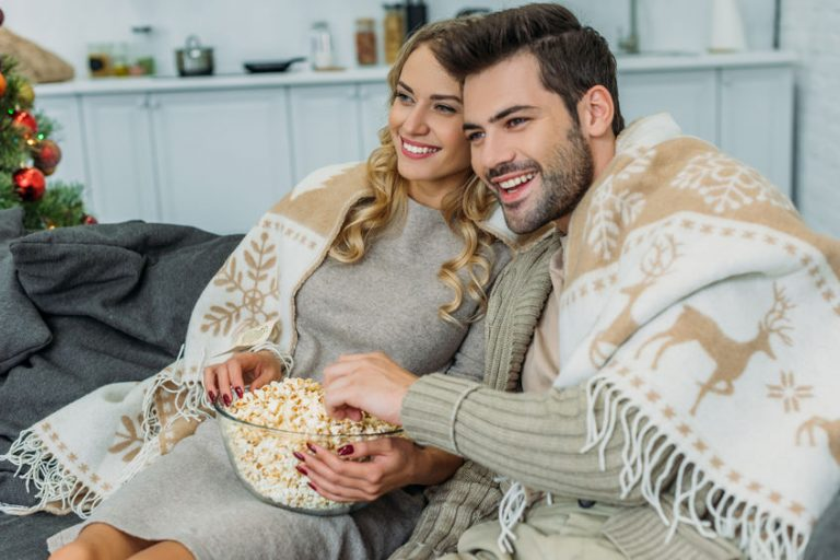 Coppia sul divano mangiando popcorn