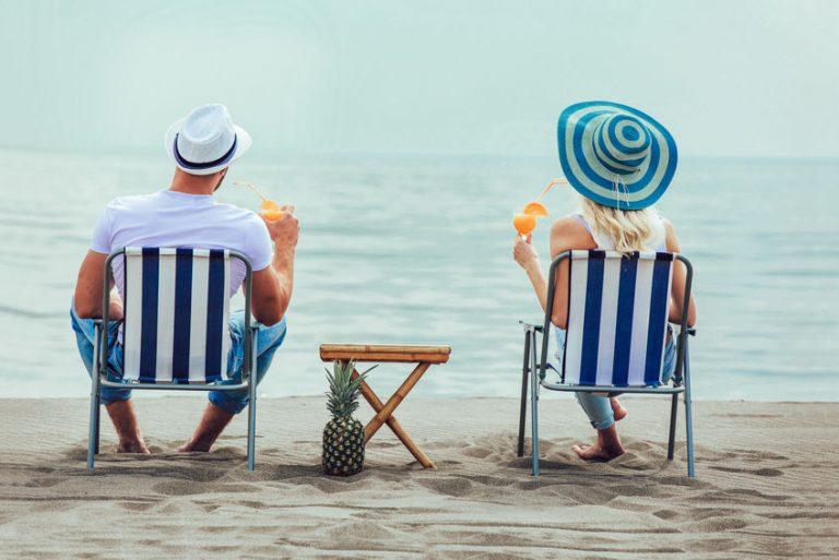 Coppia con sedie da spiaggia fronte mare