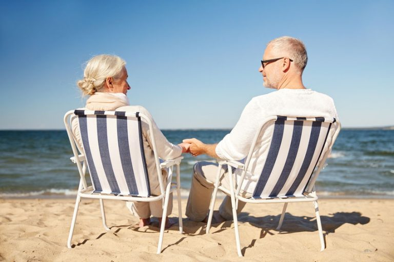 Anziani seduti sulle sedie da spiaggia in riva al mare