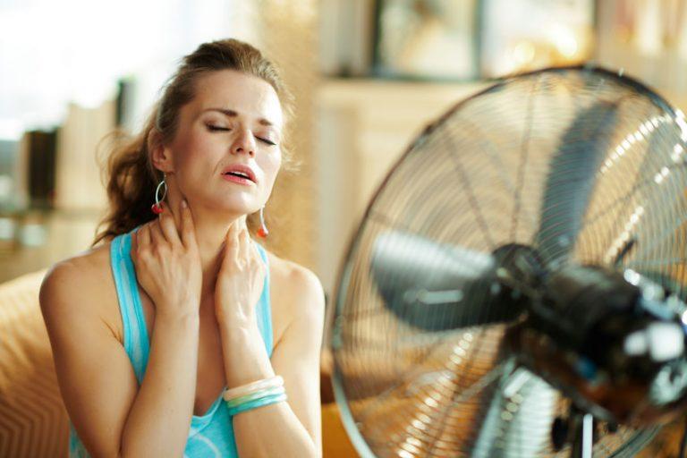 Donna che soffre il caldo davanti al ventilatore