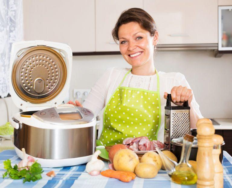 Donna accanto a una pentola elettrica e vari ingredienti