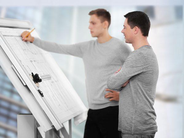 Due uomini davanti a un tavolo da disegno professionale
