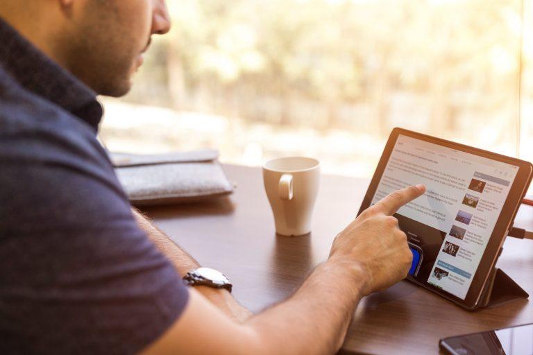Uomo che usa il tablet accanto a un caffè