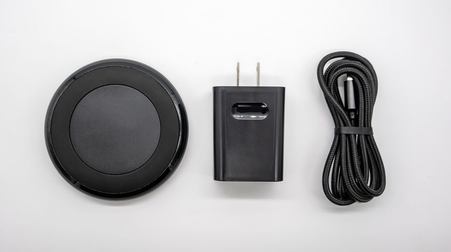 Black round shape wireless charger and adapter isolated on white