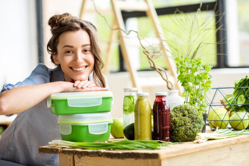 Una giovane donna seduta con le mani su due scatole da pranzo verdi una sull'altra