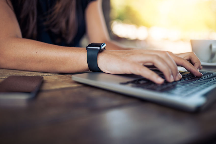 Woman with smartwatch working on laptop