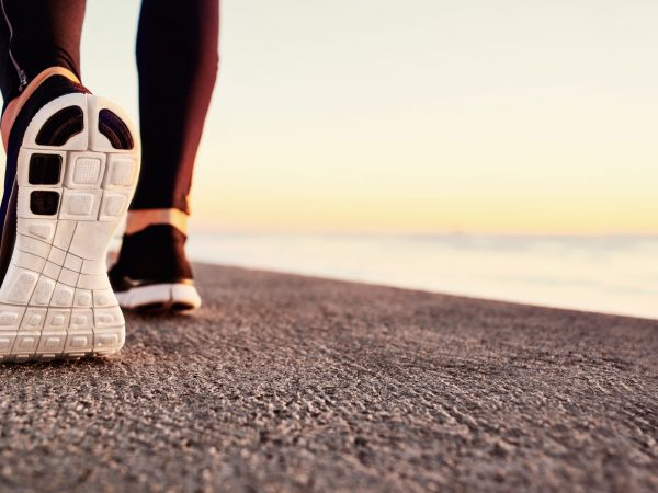 Runner man feet running on road closeup on shoe. Male fitness athlete jogger workout in wellness concept at sunrise. Sports healthy lifestyle concept