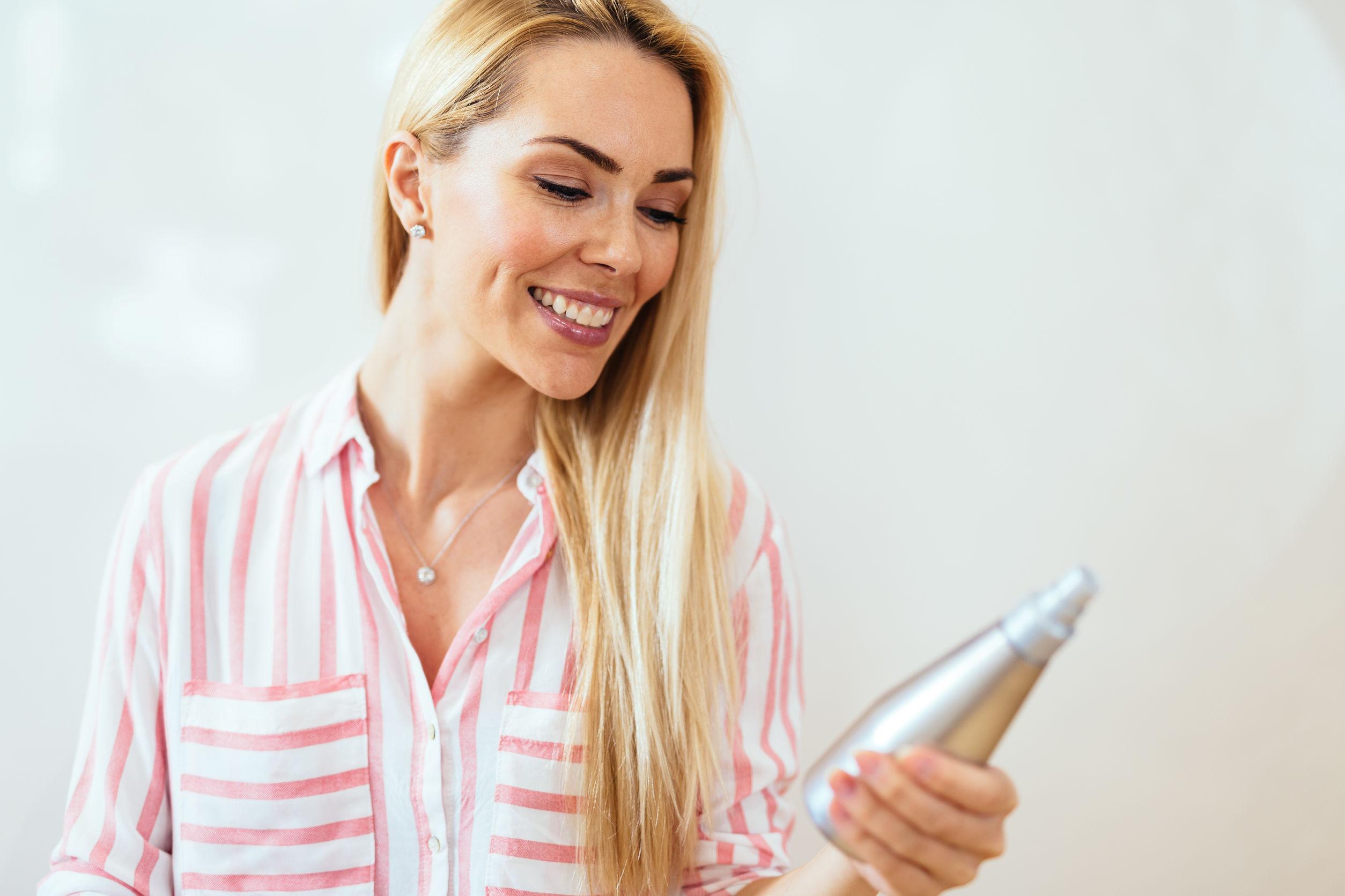 Donna che sorride con un prodotto in mano