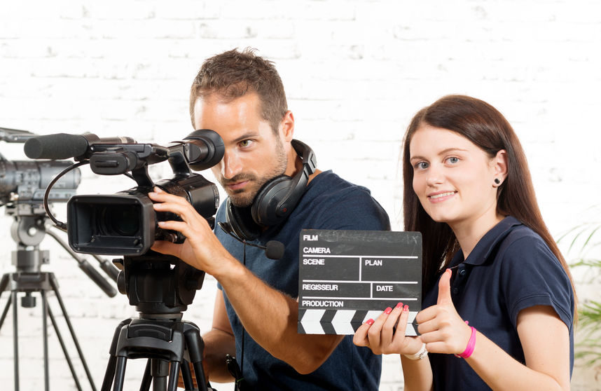 a cameraman and a young woman with a movie camera