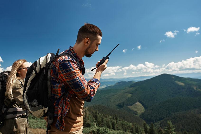 Uomo che usa un walkie talkie in montagna