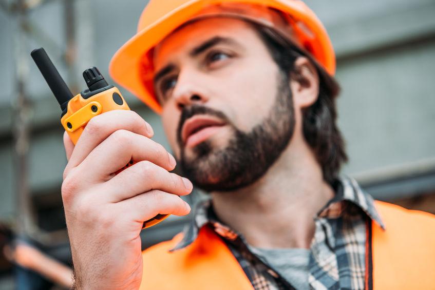 Uomo che usa un walkie talkie a lavoro