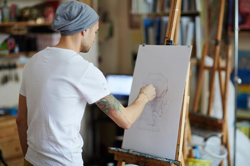 Uomo che disegna usando un cavalletto
