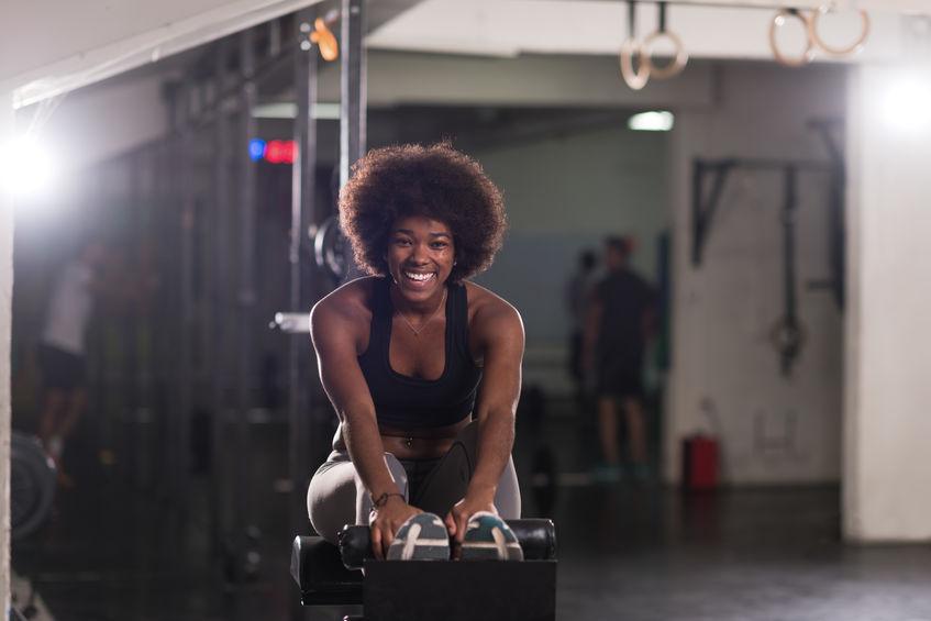 Donna che sorride su una panca per addominali