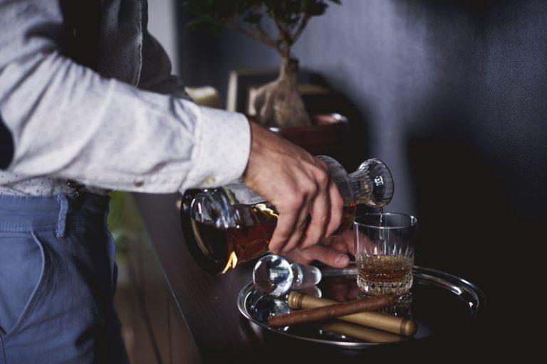 Persona che versa alcol in un bicchiere