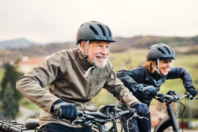 Due persone in bicicletta con il casco