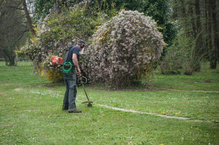 Giardiniere che usa un decespugliatore