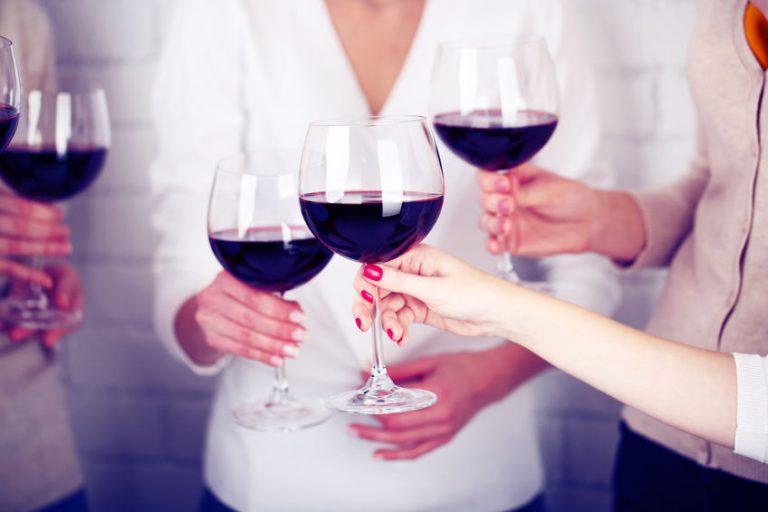 Brindisi con bicchieri di vino rosso