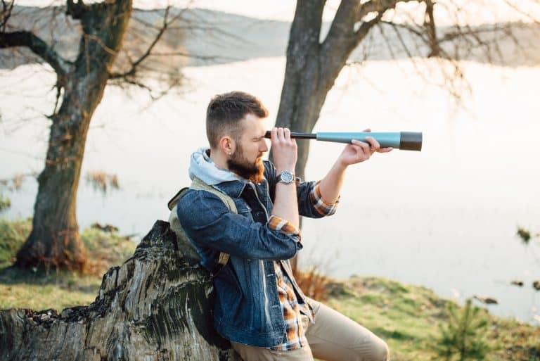 Uomo che osserva la natura con un telescopio terrestre